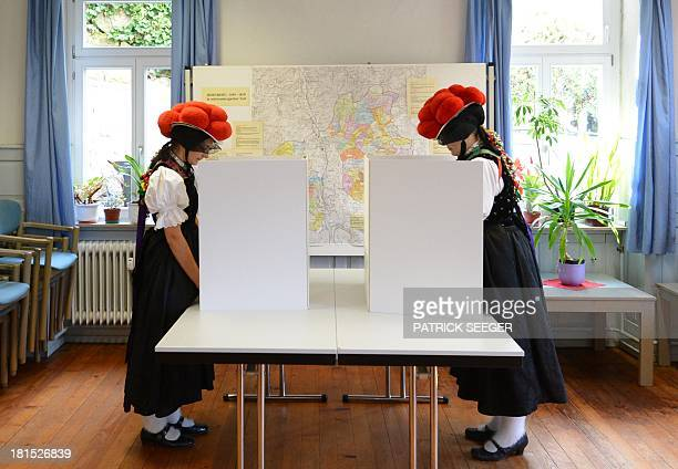 Voters Gerlinde Moser and Corinna Wöhrle wear a Black Forest traditional clothes and the pompoms hat 'Bollenhut' as they cast their ballot at a...