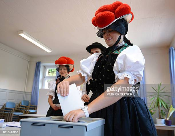 Voters Gerlinde Moser Christoph Wöhrle and Corinna Wöhrle wear Black Forest traditional clothes and the pompoms hat 'Bollenhut' as they queue to cast...