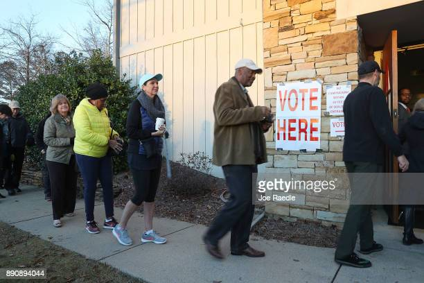 Voters head in to cast their ballot as the doors open at a polling station setup in the St Thomas Episcopal Church on December 12 2017 in Birmingham...