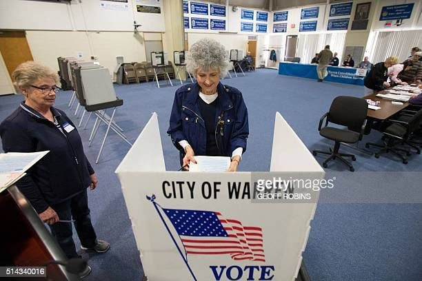 Voters line up to cast ballots for the Michigan presidential primary at a polling station in Warren Michigan March 8 2016 US voters cast ballots in...