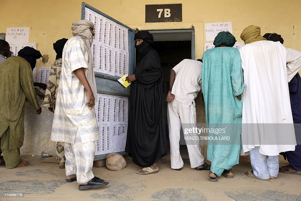 Voters look for their names on the list of biometric voters at the entrance at a polling station on July 28, 2013 in Kidal in northern Mali. AFP PHOTO / KENZO TRIBOUILLARD
