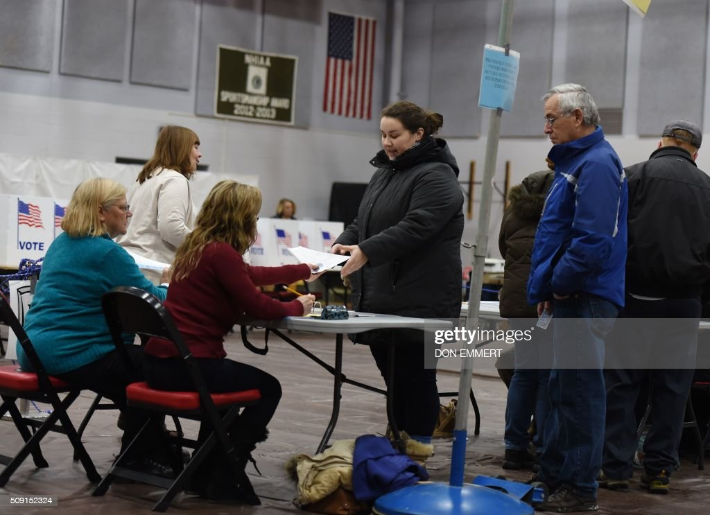Voters pick up their ballots to vote at Belmont High School February 9, 2016 in Belmont New Hampshire. Voting began in New Hampshire on Tuesday in the first US presidential primary, where Donald Trump leads the packed Republican field and Bernie Sanders was polling ahead of Hillary Clinton. Despite its small size New Hampshire's spot on the electoral calendar gives it special importance in the long state-by-state battle to select the Republican and Democratic candidates who will go head to head for the White House. / AFP / Don EMMERT