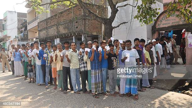 Voters pose with their cards for picture as they wait in a long queue to cast votes during the first phase of Bihar Assembly polls outside a polling...