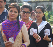 Voters pose with their cards for picture as they wait in a long queue to cast their votes during the first phase of Bihar Assembly polls at...