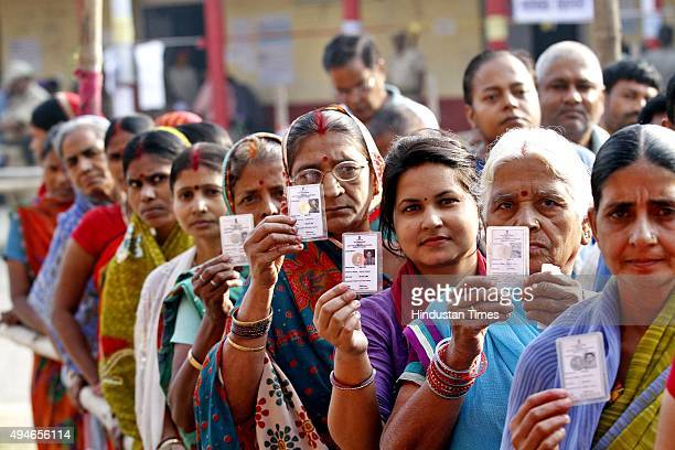 Voters pose with their ID Cards standing in queue to cast their votes at DAV School Danapur Cantt during the third phase of Bihar Assembly Elections...
