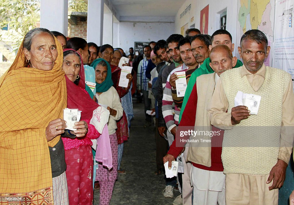 Voters pose with their identifaction papers as they queue at a polling station for the Himachal Assembly election in Mandi on November 4, 2012 in Himachal Pardesh, India. Voting figures have indicated a high percentage turnout for polling in the assembly election.