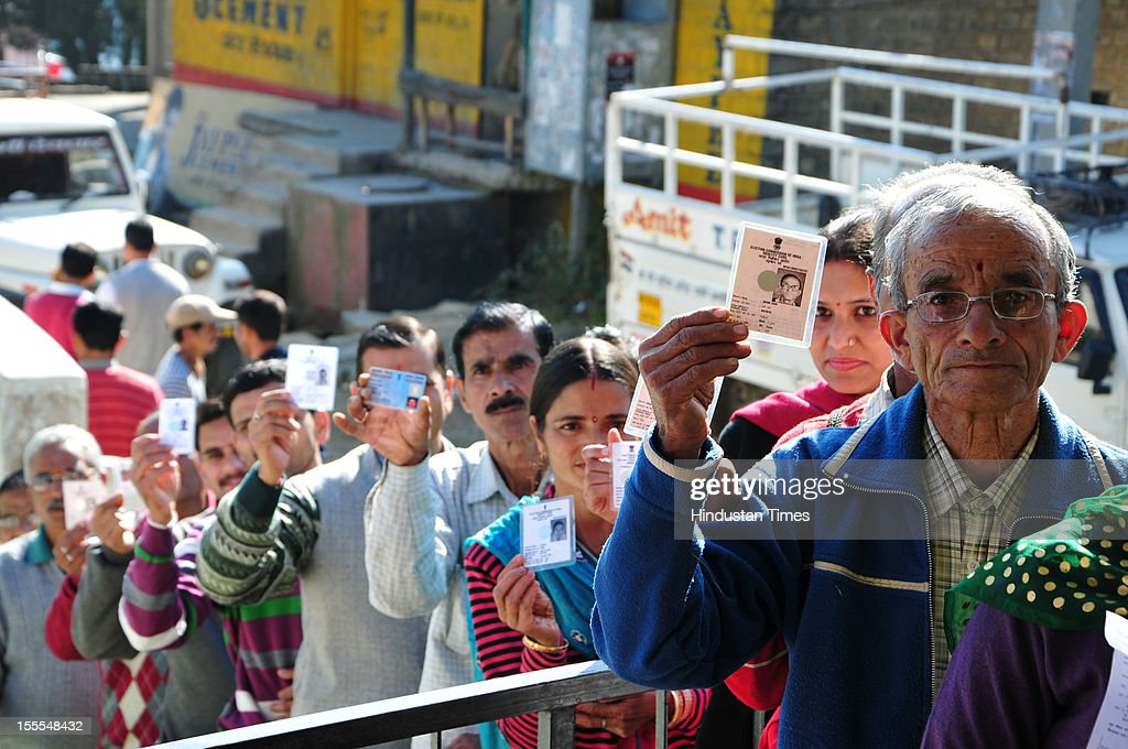 Voters pose with their identification papers as they queue outside a polling station for the Himachal Assembly election at Kelti in Shimla, on November 04, 2012 in Himachal Pardesh, India. Voting figures have indicated a high percentage turnout for polling in the assembly election.