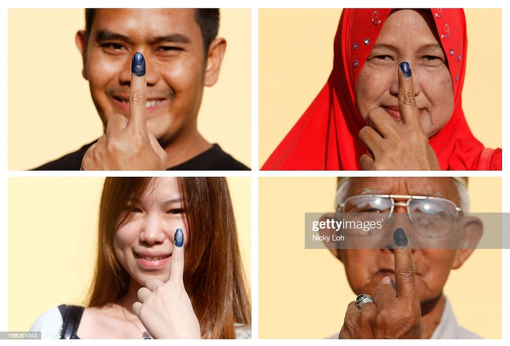 Voters pose with their inked fingers at a polling station during election day on May 5, 2013 in Pekan, Malaysia. Millions of Malaysians casted their vote on Sunday in one of the most tightly contested Malaysian election since independence in 1957. The opposition coalition, Pakatan Rakyat (PeopleÕs Alliance), led by former deputy prime minister Anwar Ibrahim is seeking to gain power on a national level against the ruling party Barisan Nasional.