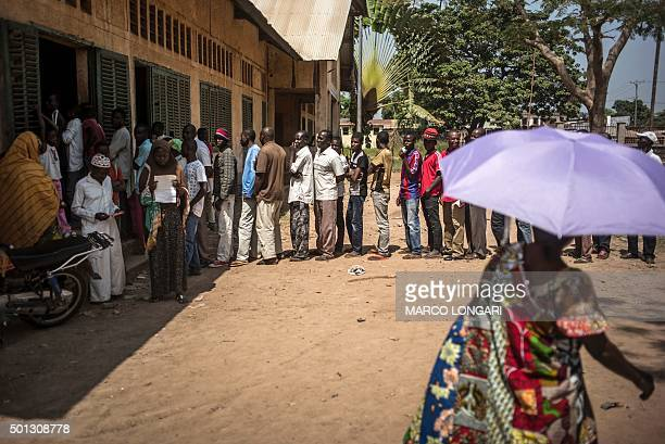 Voters queue at the polling station at the Koudoukou school in the flashpoint PK5 district in Bangui on December 14 2015 where voting operations for...