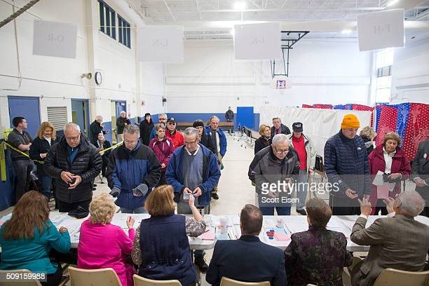 Voters show indentification to poll workers before entering the polling booths inside the Webster School gymnasium February 9 2016 in Manchester New...