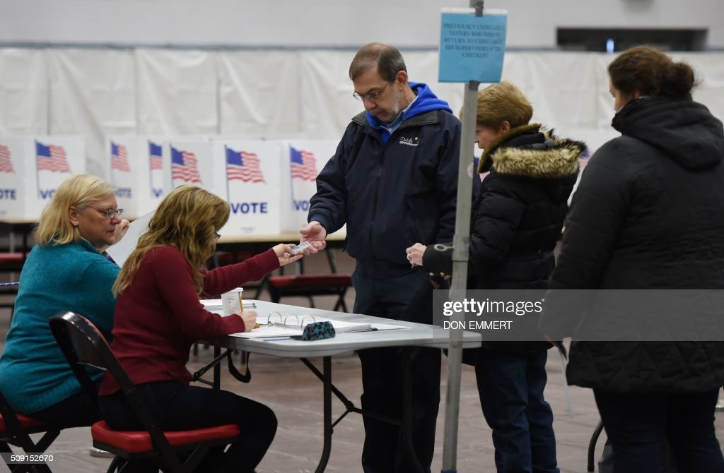 Voter's show their identification to polling station workers as they prepare to cast ballots at Belmont High School February 9, 2016 in Belmont New Hampshire. Voting began in New Hampshire on Tuesday in the first US presidential primary, where Donald Trump leads the packed Republican field and Bernie Sanders was polling ahead of Hillary Clinton. Despite its small size New Hampshire's spot on the electoral calendar gives it special importance in the long state-by-state battle to select the Republican and Democratic candidates who will go head to head for the White House. / AFP / Don EMMERT