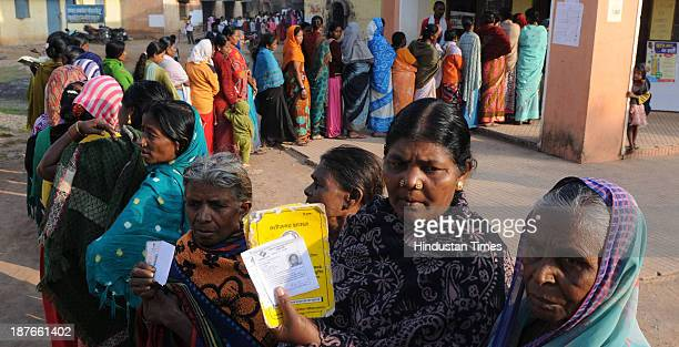 Voters showing their Id cards standing in queue to cast their vote at polling booth during the first phase of assembly elections of Chhattisgarh at...