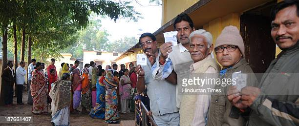 Voters showing their voter Id card standing in queue to cast their vote at polling booth during the first phase of assembly elections of Chhattisgarh...