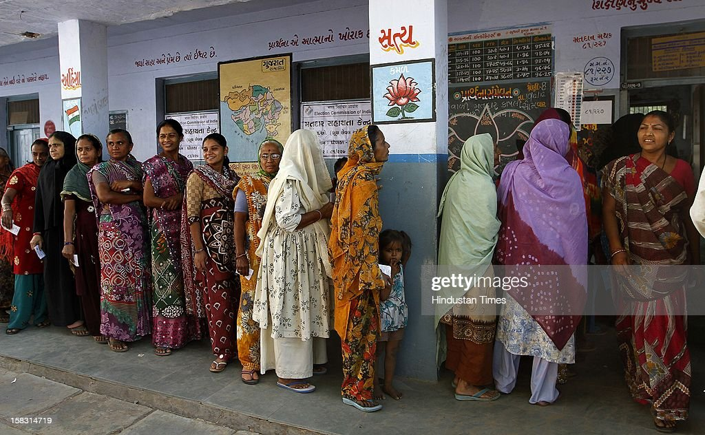 Voters standing in queue to cast their vote as a Lotus flower seen painted at the background which is also the symbol of BJP during the first phase polling of Gujarat assembly election at Dholka on December 13, 2012 in Ahmedabad, India.