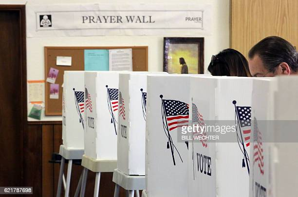 Voters vote in front of a Prayer Wall at a polling station at the Big Bear Lake Methodist Church in Big Bear California November 8 2016 / AFP / Bill...