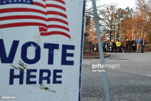 Voters wait in line to cast their ballot at a polling station setup in the St Thomas Episcopal Church on December 12 2017 in Birmingham Alabama...