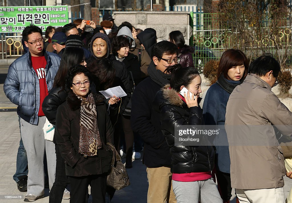 Voters wait in line to cast their ballots for the presidential election at a polling station in Seoul, South Korea, on Wednesday, Dec. 19, 2012. South Koreans go to the polls today to choose either a dictator's daughter or a one-time dissident as president, both of whom pledge to reverse slowing growth, a widening income gap and deteriorating North Korea ties. Photographer: SeongJoon Cho/Bloomberg via Getty Images