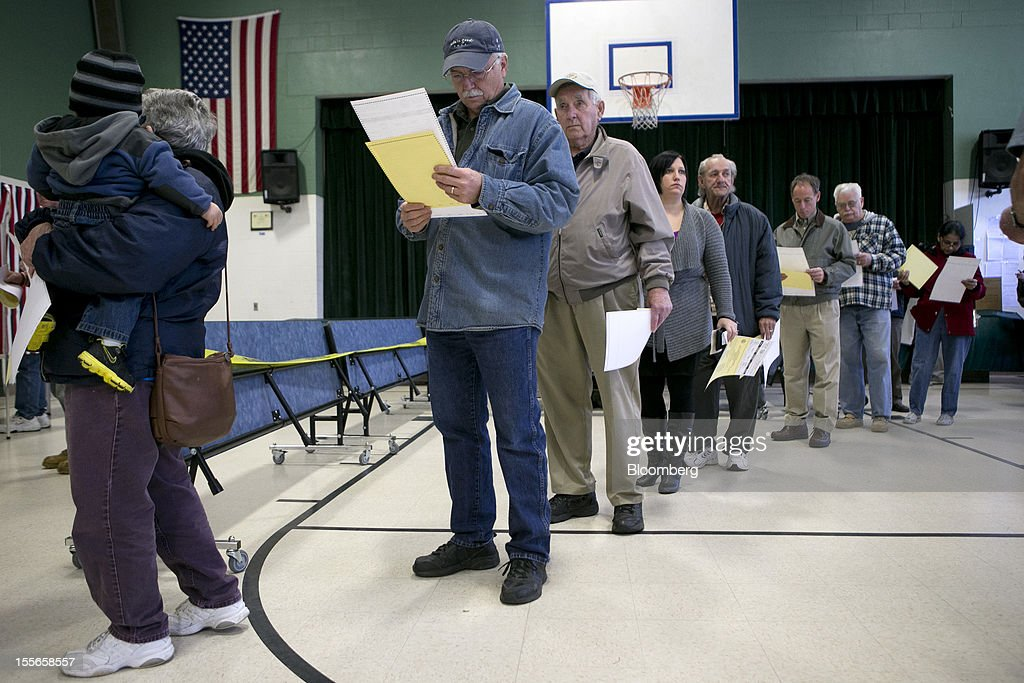 Voters wait to fill out their ballots at a polling station in Manchester, New Hampshire, U.S., on Tuesday, Nov. 6, 2012. U.S. President Obama is seeking to overcome the drag of high unemployment and economic weakness that has frustrated predecessors' re-election bids, while his Republican rival Mitt Romney reaches for an upset to propel him beyond his party's standing and swamp an electoral map stacked against him on the final day of the presidential race. Photographer: Andrew Harrer/Bloomberg via Getty Images