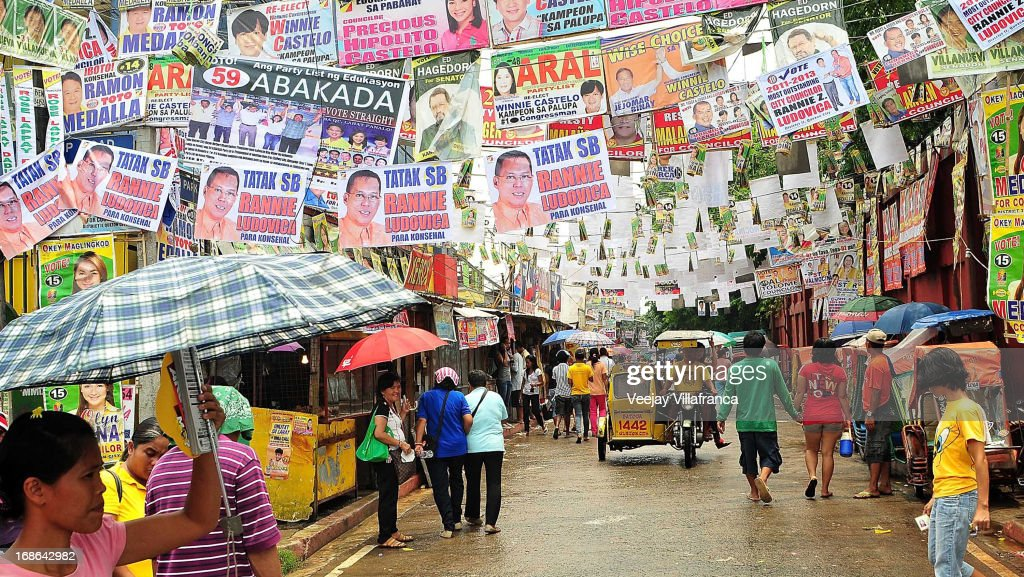 Voters walk beneath election posters, suspended over a street in a polling precinct May 13, 2013 in Manila, Philippines. Millions of Filipinos are heading out to cast their votes for the mid-term election today. So far, over 50 people have been killed in the run up to polling day for the elections that have been marred by violence and accusations of corruption and neopotism.