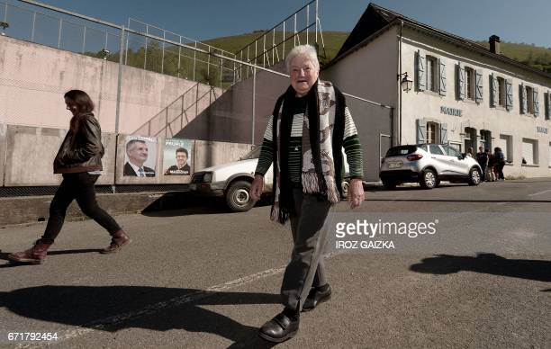 Voters walk past election campaign posters for French lawmaker and independent candidate for Jean Lassalle and candidate for the farleft coalition La...