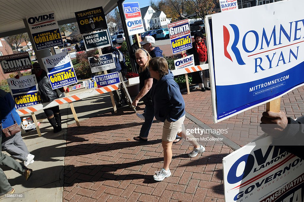 Voters walk past supporters holding signs on their way to casting ballots at Northwest Elementary School November 6, 2012 in Manchester, New Hampshire. The race between incumbent President Barack Obama and Republican challenger Mitt Romney will come down to certain swing states like New Hampshire.