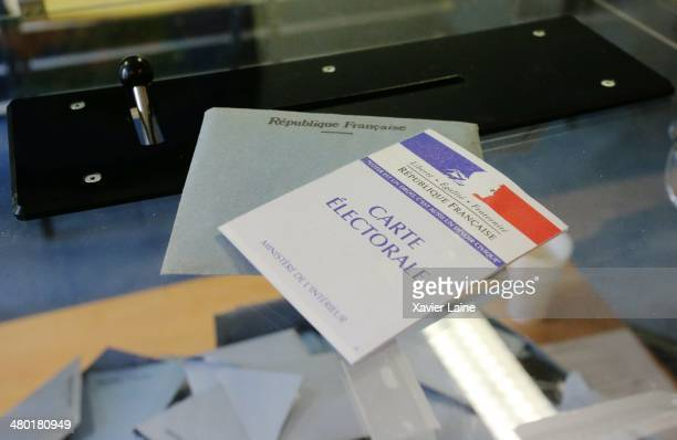 A voting card is displayed in the 20th district as French voters go to the polls to vote in the municipal elections on March 23 2014 in Paris France...