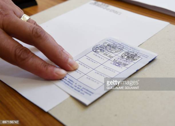A voting card with the dates of the first and second round of the French legislative election is pictured at a polling station in Authon northern...
