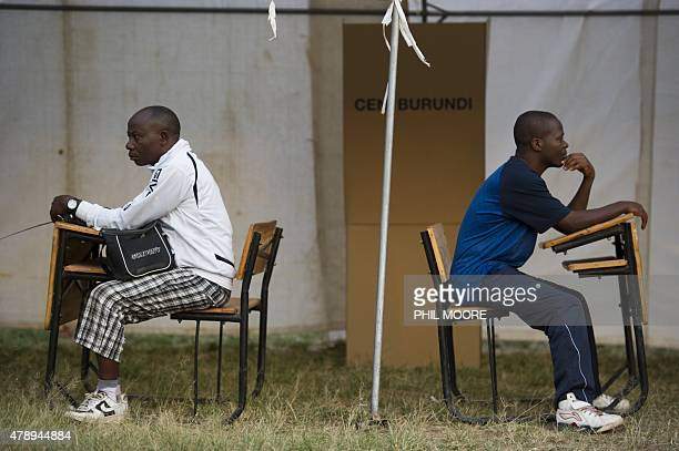 Voting officials wait for the delayed opening of polling in a voting station in the opposition stronghold of Musaga in Bujumbura on June 29 2015...