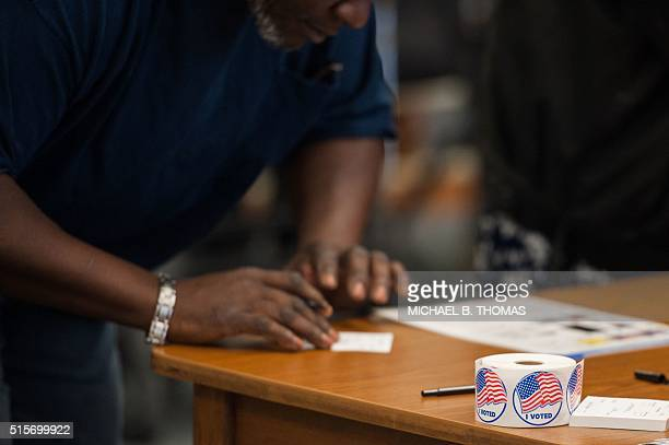 Voting stickers are seen as a man is checked in to receive his ballot during Missouri primary voting at the Griffith Elementary School on March 15...