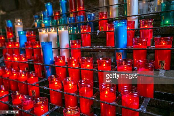 Votive Candles burning in front of out of focus lights