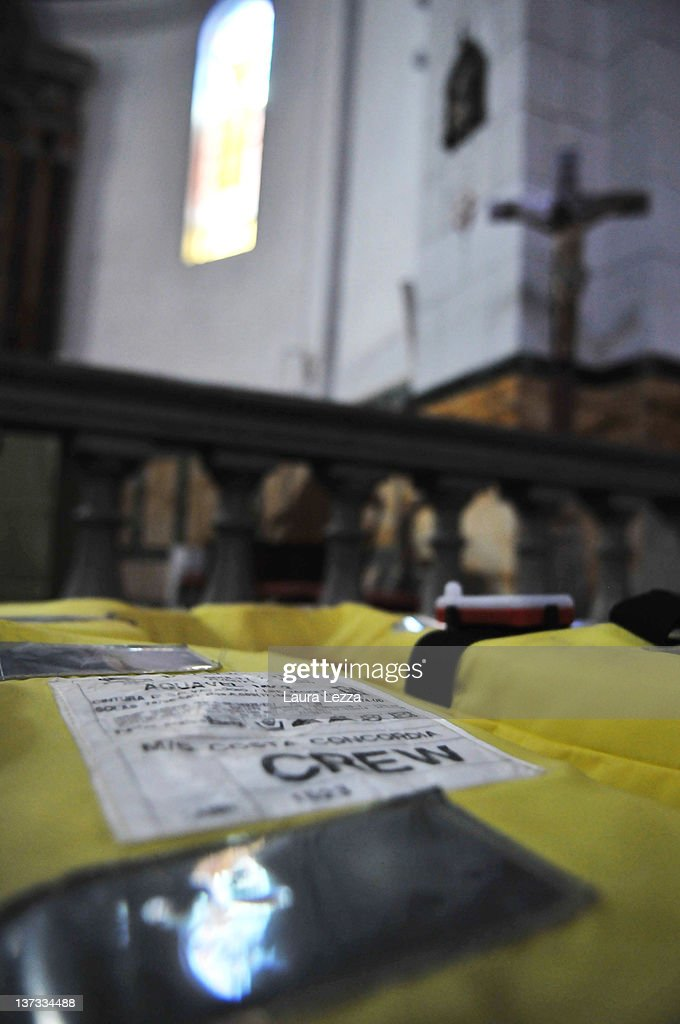 Votive objects are left by passengers who survived the grounding of cruise liner Costa Concordia at the Church of San Lorenzo on January 19, 2012 in Giglio Porto, Italy. The church has also been a refuge for people who have visited to pray for missing relatives. More than four thousand people were onboard when the ship hit a rock off the Tuscan coast. At least 11 people have been confirmed dead while more than 20 remain missing. Rescue divers today resumed their search of the cruise liner's hull.