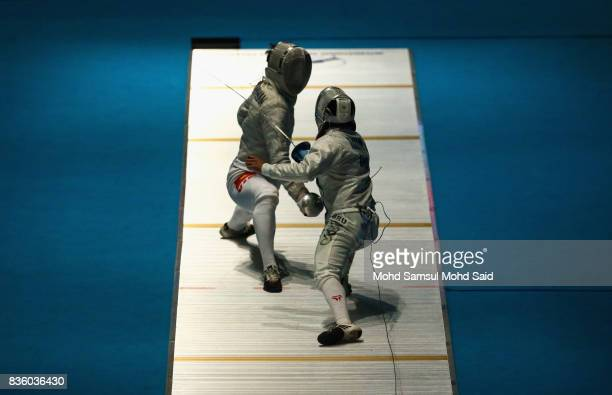 Vu Thanh An of Vietnam competes against Mohammad Hardiwan of Brunei during the Men's Sabre Individual fencing match at the 2017 SEA Games on August...