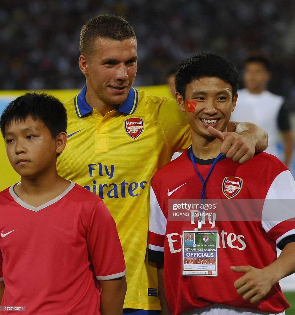 Vu Xuan Tien (R) a Vietnamese football fan who is dubbed the 'Running Man' after chasing Arsenal's team bus five miles through the streets of Hanoi, poses with Arsenal's Lukas Podolski prior to a friendly match between the English Premier League team Arsenal and Vietnam's national team at Hanoi's My Dinh stadium on July 17, 2013. Arsenal who are on a three-day visit in Hanoi, the second leg of its Asian tour after Indonesia, won 7-1. AFP PHOTO/HOANG DINH Nam