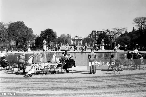 Vue du Grand Bassin Octogonal du Jardin des Tuileries et son loueur de bateaux photographié à Paris dans les années 50 Au fond l'Arc du Carrousel /...