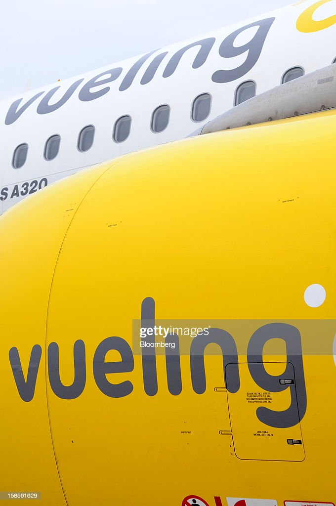A Vueling Airlines SA logo is seen on an Airbus A320 engine cowling and fuselage at EL Prat airport in Barcelona, Spain, on Wednesday, Dec. 19, 2012. International Consolidated Airlines Group SA won't require European Union approval to buy 100 percent of low-cost carrier Vueling Airlines SA, the EU's antitrust chief said. Photographer: Stefano Buonamici/Bloomberg via Getty Images