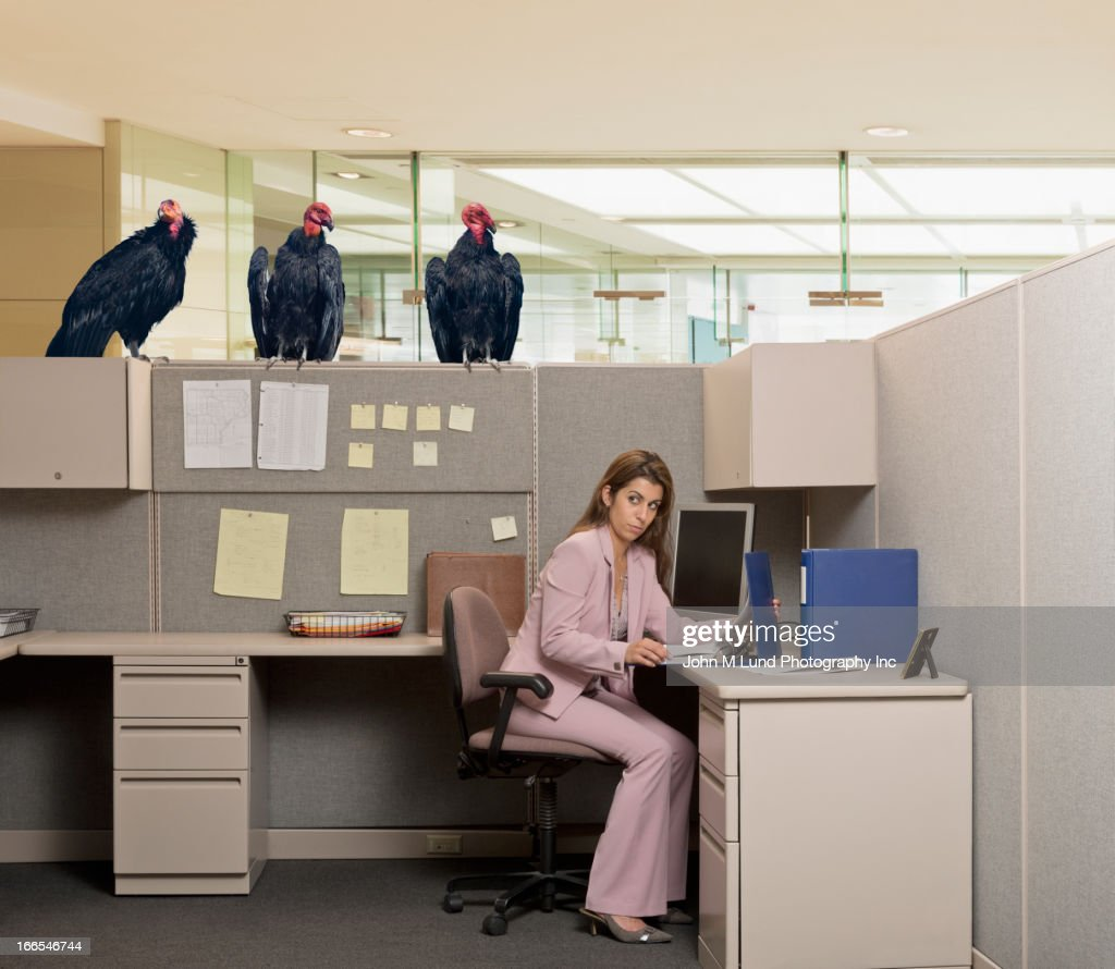 Vultures watching Hispanic businesswoman at desk