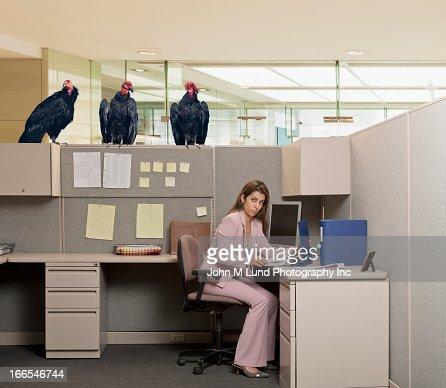 Vultures watching Hispanic businesswoman at desk