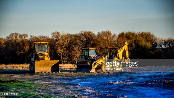 Waco, TX, USA February 8, 2017:Two yellow earth movers, a bulldozer and back hoe/front loader, sit idle on a construction site illuminated by the early morning sun.