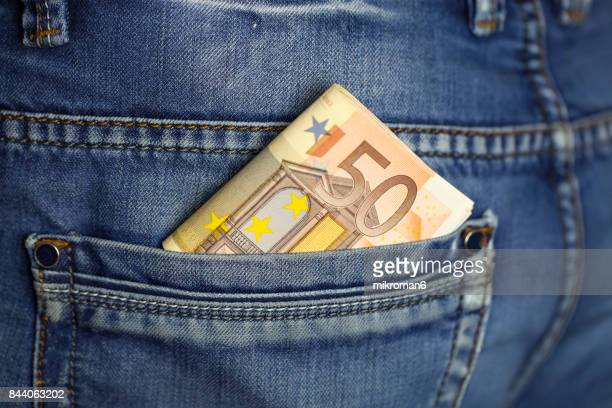 Wad of cash into the pocket of jeans
