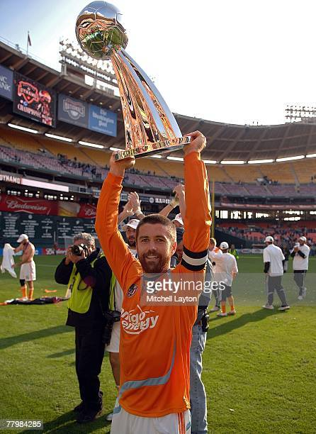 Wade Barrett of the Houston Dynamo celebrates with the trophy after defeating the New England Revolution by a score of 21 to win the 2007 Major...