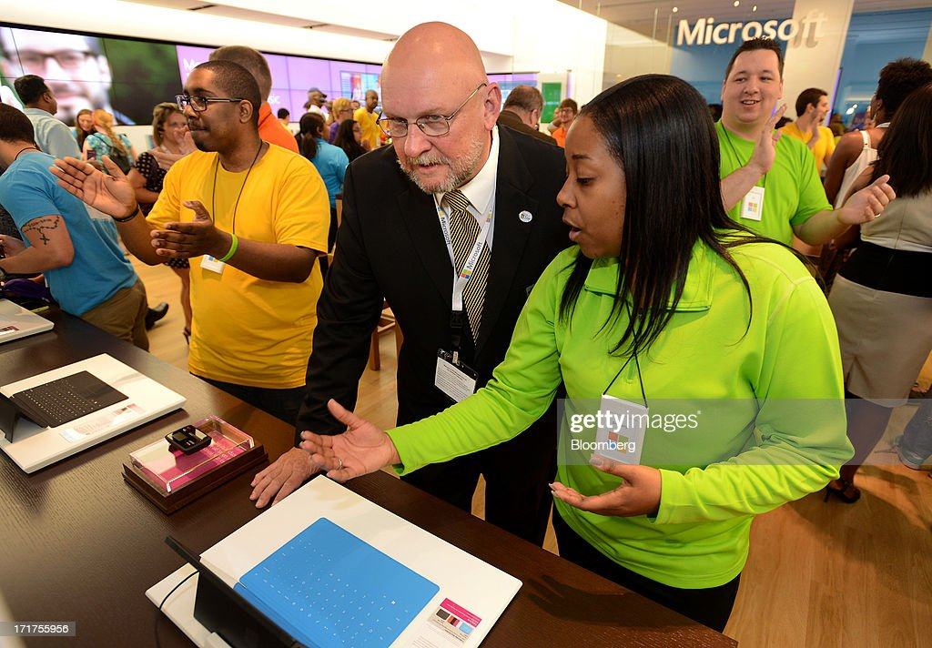 Wade Fleming, mayor pro-tem of Troy, center, speaks with employee Brittany Sanders, right, about the Surface tablet system during the grand opening of a Microsoft Corp. store in Troy, Michigan, U.S., on, Friday, June 28, 2013. Microsoft, which has been struggling with the inability of outside retailers to effectively display its products, aims to generate more enthusiasm for them by opening its own stores. Photographer: Bryan Mitchell/Bloomberg via Getty Images