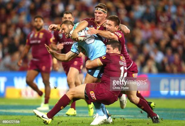 Wade Graham of the Blues is tackled by Matt Gillett and Josh McGuire of the Maroons during game one of the State Of Origin series between the...