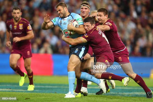 Wade Graham of the Blues is tcakled during game one of the State Of Origin series between the Queensland Maroons and the New South Wales Blues at...