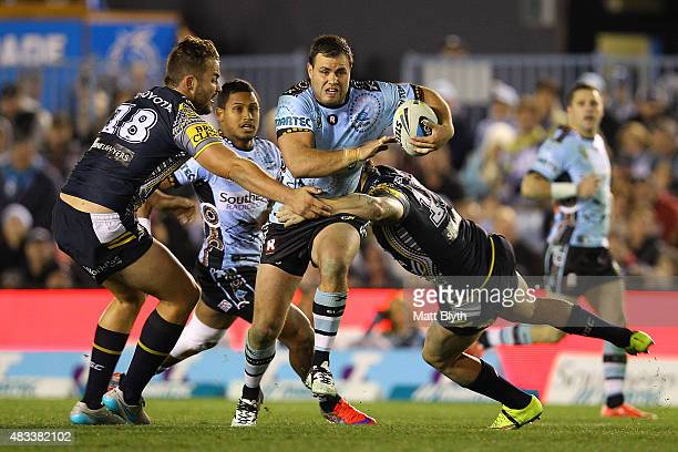 Wade Graham of the Sharks is tackled during the round 22 NRL match between the Cronulla Sharks and the North Queensland Cowboys at Remondis Stadium...