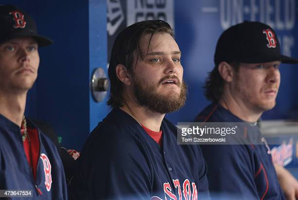 Wade Miley of the Boston Red Sox looks on from the dugout as he sits between Clay Buchholz and Ryan Hanigan during MLB game action against the...