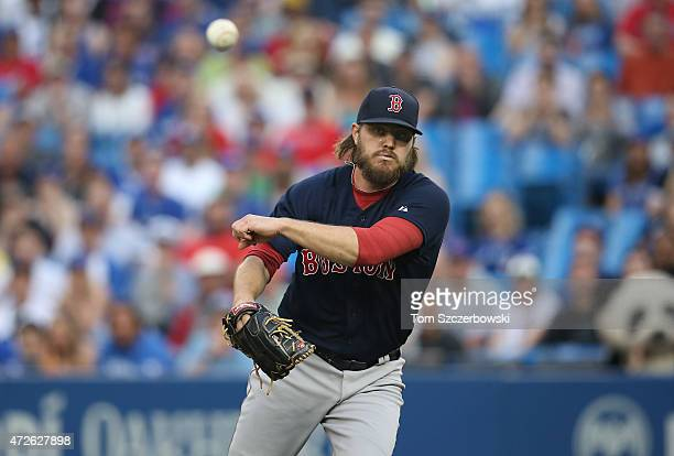 Wade Miley of the Boston Red Sox picks Jose Bautista of the Toronto Blue Jays off third base to begin a rundown in the first inning during MLB game...