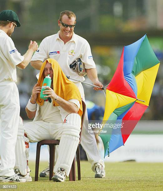 Wade Seccombe of Australia loses control of an umbrella he was using to shade Darren Lehmann of Australia during the drinks break during day four of...