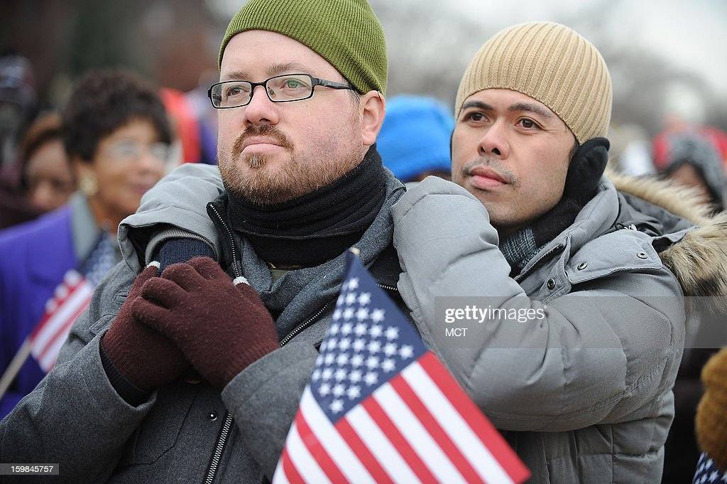 Wade Trefethen, 38 and right Sunny Valencia, 31, both of New York City, wait on the National Mall for President Barack Obama to take the oath of officeMonday, January 21, 2013.
