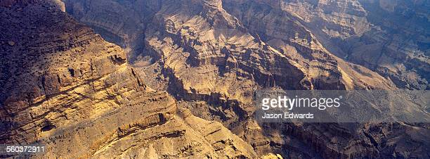 Sheer cliff walls and terraces carved by erosion in a massive desert canyon.