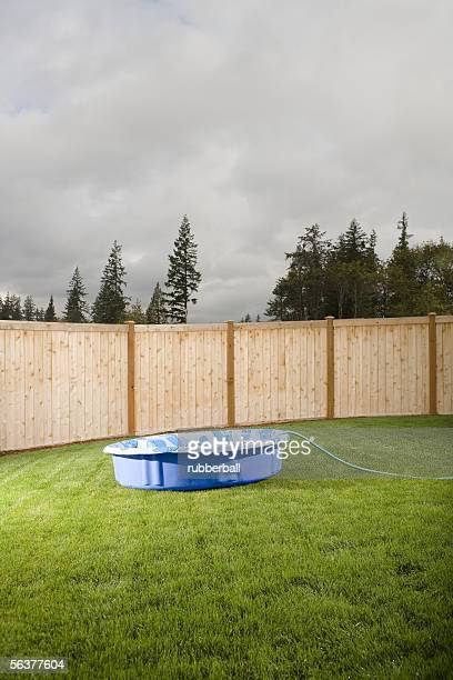 Wading pool with hose on a lawn